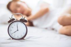 Красивая азиатская молодая женщина поворачивает будильник в добром утре, бодрствовании вверх для сна Стоковое фото RF