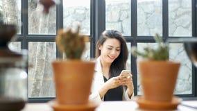 Красивая азиатская молодая куртка костюма носки бизнес-леди используя применение на болтовне умного телефона отправляя СМС с друг