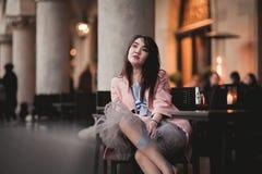 Красивая азиатская модель девушки в платье сидя на старой предпосылке города Стоковые Изображения RF