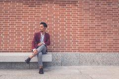 Красивая азиатская модель сидя в улицах города Стоковые Изображения RF
