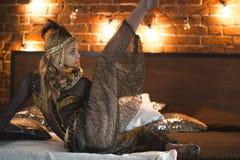 Красивая актриса цирка выполняя танец с змейкой на кровати Стоковое Фото