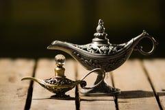 Красивая античная лампа металла в истинном стиле Aladin, более малой модели помещенной рядом с ним, сидящ на деревянной поверхнос Стоковые Изображения