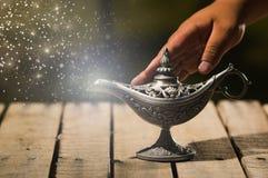 Красивая античная лампа металла в истинном стиле Aladin, рука касающая и оживленная пыль звезды приходя вне, сидящ на деревянном Стоковое Изображение