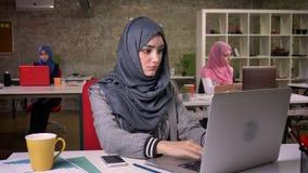 Красивая арабская женщина в сером славном hijab печатает на ее ноутбуке, отделенном от других мусульманских девушек за ей, соврем акции видеоматериалы
