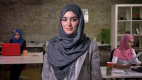 Красивая аравийская девушка в сером hijab смотрит холодок на камере пока стоящ прямые, арабские девушки на предпосылке сток-видео