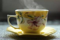 Красивая ароматичная и горячая чашка кофе с поддонником около окна раньше на утре Стоковая Фотография RF