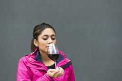 Красивая латинская женщина пахнуть красным вином над серой предпосылкой стоковое фото rf