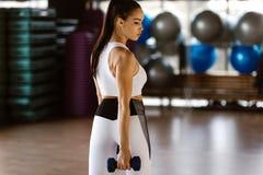 Красивая атлетическая девушка одетая в белой верхней части спорт и строения колготков поднимают мышцы с гантелями стоковые фотографии rf