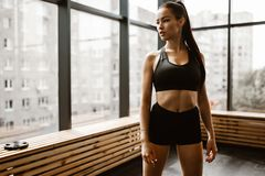 Красивая атлетическая девушка с каштановыми волосами одетыми в черных спорт верхних и стойках шортов в спортзале стоковая фотография rf