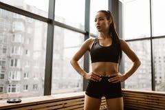 Красивая атлетическая девушка с каштановыми волосами одетыми в черных спорт верхних и стойках шортов в спортзале стоковое фото rf
