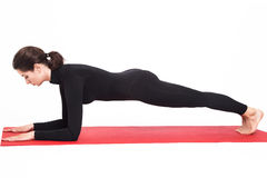 Красивая атлетическая девушка в черном костюме делая йогу Представление планки asana Kumbhasana на локти Изолированная белая пред Стоковые Фотографии RF