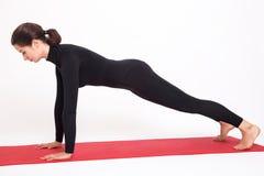 Красивая атлетическая девушка в черном костюме делая йогу Представление планки asana Kumbhasana белизна изолированная предпосылко Стоковая Фотография RF