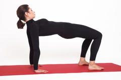 Красивая атлетическая девушка в черном костюме делая йогу Представление планки asana Purvottanasana На белой предпосылке Стоковое Фото