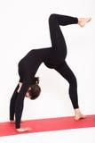 Красивая атлетическая девушка в черном костюме делая йогу chakrasana - представление моста белизна изолированная предпосылкой Стоковые Изображения RF