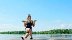 Красивая, атлетическая молодая белокурая женщина делая различные тренировки с весами, гантелями, выпадами, сидит на корточках Озе видеоматериал