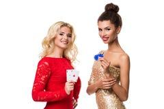 Красивая африканская женщина и кавказская молодая женщина с длинными светлыми белокурыми волосами в обмундировании вечера Держать стоковое фото