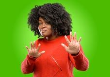 Красивая африканская женщина при вьющиеся волосы изолированное над зеленой предпосылкой стоковая фотография