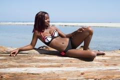 Красивая африканская женщина сидя на пляже Стоковые Изображения