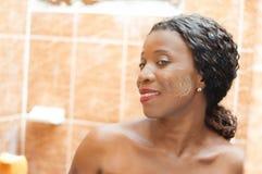 Красивая африканская женщина усмехаясь с сливк на ее стороне стоковые фото