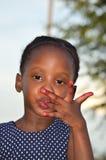 Красивая африканская чернота лижа ее пальцы Стоковое Изображение