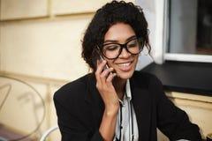 Красивая Афро-американская девушка в стеклах сидя на таблице кафа и говоря на ее мобильном телефоне Милая дама с Стоковые Фото