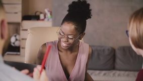 Красивая Афро-американская коммерсантка сидит вниз таблицей, улыбками на многонациональных коллегах на встрече офиса сток-видео