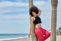 Красивая афро американская склонность женщины против ладони на пляже Стоковое Фото