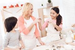 Красивая бабушка, вместе с малыми внуками в кухне, выбирает прессформы печенья стоковое фото rf