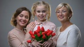Красивая бабушка и мать обнимая дочь с тюльпанами в руках, поколениях сток-видео