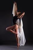 Красивая балерина женщины в костюме черного тела танцуя над серым цветом Стоковое Изображение