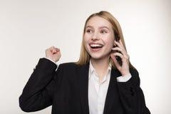 Красивая белокурая дама дела в черном костюме говорит на мобильном телефоне и усмехаться стоковые фотографии rf