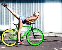 Красивая белокурая девушка делая фокусы и имея потеху на крутом зеленом фиксированном велосипеде в парке города Европы стоковые изображения
