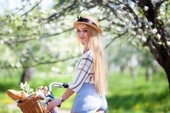 Красивая белокурая девушка идя с ретро велосипедами в солнечном славном дне, нося винтажных одеждах битника и шляпах Положительно стоковая фотография