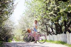 Красивая белокурая девушка идя с ретро велосипедами в солнечном славном дне, нося винтажных одеждах битника и шляпах Положительно стоковое изображение