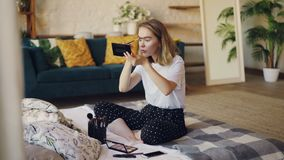 Красивая белокурая девушка кладет на брови картины состава при набор щетки и косметик сидя на кровати дома бобра видеоматериал