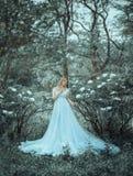 Красивая белокурая девушка, модельный размер плюс, идет в ботанический, зацветая сад против фона pioneering пиона _ Стоковое Изображение