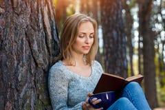 Красивая белокурая девушка отдыхая весной или лес осени прочитали книгу и сидеть с чашкой чаю и книгой уверенно Стоковые Фото