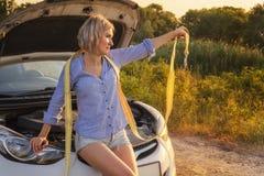 Красивая белокурая девушка сидит с towline на клобуке сломленного автомобиля на сельской дороге в лучах захода солнца Стоковые Фотографии RF