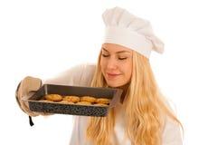Красивая белокурая женщина в платье шеф-повара печет печенья изолированные сверх стоковые изображения
