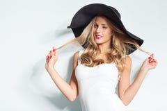 Красивая белокурая женщина в черной шляпе и белом элегантном платье вечера представляя на изолированной предпосылке фасонируйте в стоковое фото rf