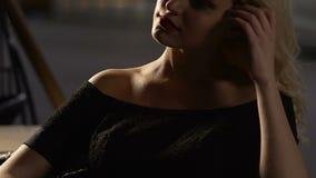 Красивая белокурая женщина сидя самостоятельно в ресторане, смертоносной женщине, самоуверенности видеоматериал