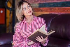 Красивая белокурая женщина с улыбкой читая и держа книгу, конец-вверх стоковые фото