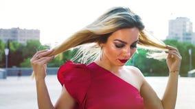 Красивая белокурая женщина с ярким макияжем касаясь ее волосам в ветре сток-видео