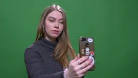 Красивая белокурая коммерсантка делая изолированные selfies используя смартфон на зеленой предпосылке chromakey видеоматериал