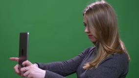 Красивая белокурая коммерсантка делая selfies используя изолированный планшет на зеленой предпосылке chromakey сток-видео