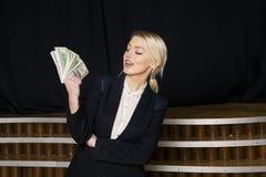Красивая белокурая коммерсантка с деньгами на офисе просторной квартиры в черном костюме Стоковое фото RF