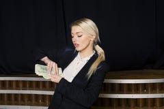 Красивая белокурая коммерсантка с деньгами на офисе просторной квартиры в черном костюме Стоковая Фотография
