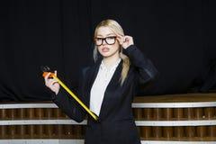 Красивая белокурая коммерсантка с рулеткой на офисе просторной квартиры в оранжевых стеклах и черном костюме владение домашнего к Стоковая Фотография