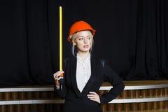 Красивая белокурая коммерсантка с рулеткой на офисе просторной квартиры в оранжевых стеклах и черном костюме владение домашнего к Стоковые Фото