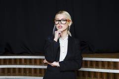 Красивая белокурая коммерсантка с тучными губами на офисе просторной квартиры в оранжевых стеклах и костюме владение домашнего кл Стоковая Фотография